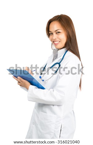 A pretty female Asian doctor with white lab coat, stethoscope looking at camera expressing warmth and empathy is smiling and writing notes on a blue clipboard of medical charts. Half V