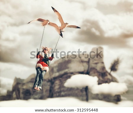 a pretty girl being carried on a swing by two seagulls in a surreal digital manipulation with a cliff and clouds in the background (FOCUS IS ON THE BIRD)  - stock photo