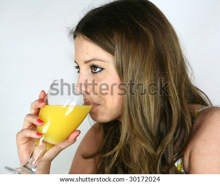 A pretty girl drinks a glass of orange juice
