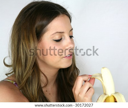 A pretty girl eats a banana for her lunch - stock photo