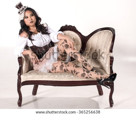 A pretty girl in steampunk reclines on a victorian chair