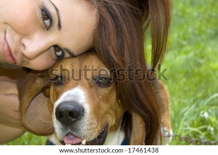 A pretty girl posing with her little beagle dog. - stock photo