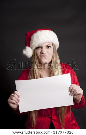 A pretty girl with a Scrooge expression on her face and Santa hat, holding a black white sign for message. - stock photo