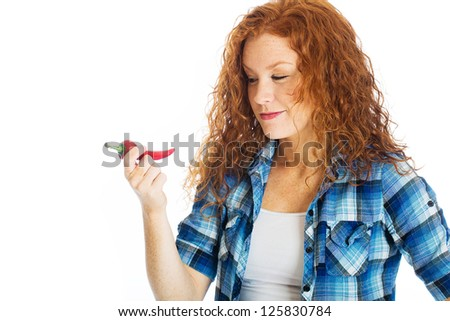 A pretty girl with red hair and freckles thinks about taking a bite out of a spicy hot red pepper. - stock photo