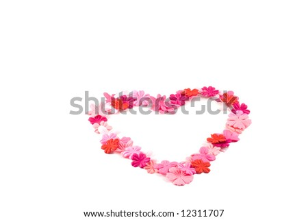 A pretty heart made out of red and pink flowers on a white background. - stock photo