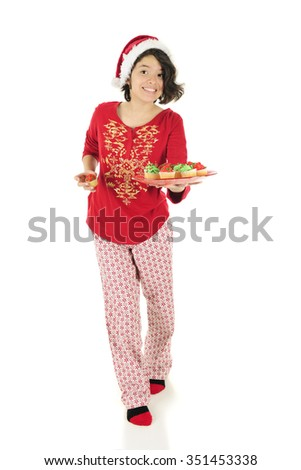 A pretty Hispanic teen offering the viewer miniature Christmas cupcakes.  She's in her pajamas and wears a Santa hat.  On a white background. - stock photo