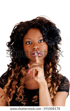 A pretty Jamaican women with long curly black and blond hair holding her finger over her mouth, isolated for white background.  - stock photo