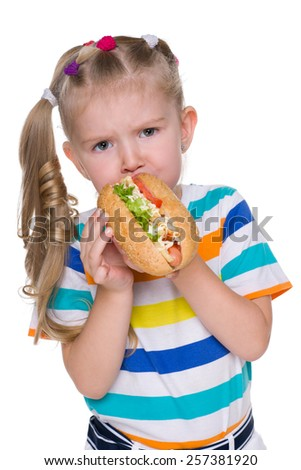 A pretty little girl eats hot dog on the white background - stock photo