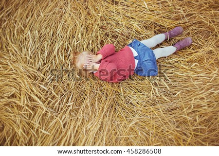A pretty little girl lies on a ears of wheat and closes his eyes - stock photo