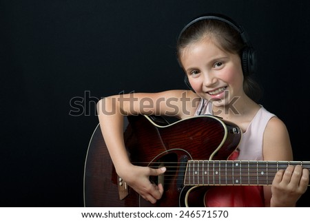 a pretty little girl whit headphones playing guitar - stock photo