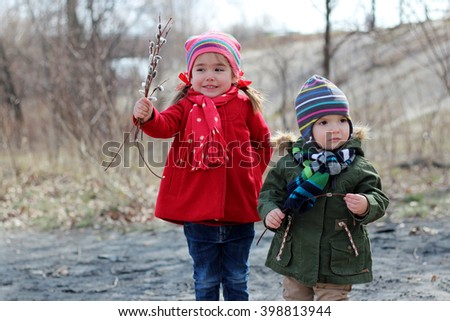 A pretty little girl with bunch of flowers, flowering willow, together with her brother walking in the forest in the sunny day, happy family weekend - stock photo