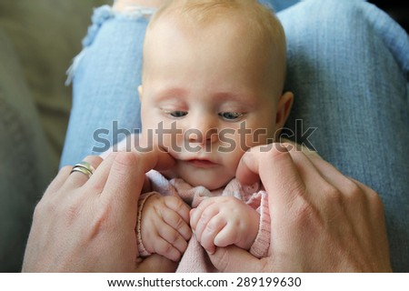 A pretty little 3 month old baby girl is sitting on her father's lap, holding both of his hands and looking at him, seen from dad's point of view.