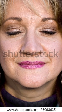 A pretty middle aged woman smiling with her eyes closed.  Shallow depth of field. - stock photo