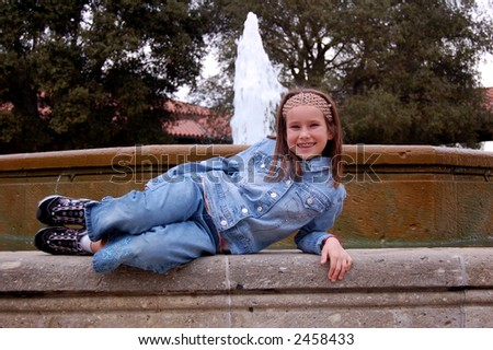 A pretty nine year old girl lying down in front of a fountain. - stock photo