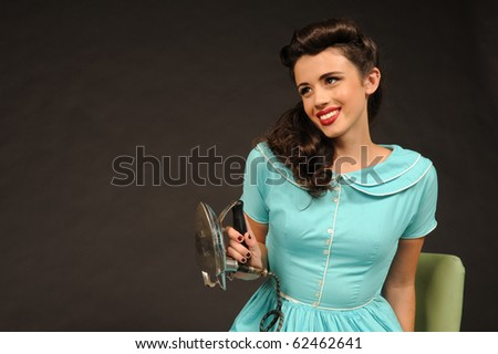 A pretty pin-up girl wearing a vintage teal dress. - stock photo