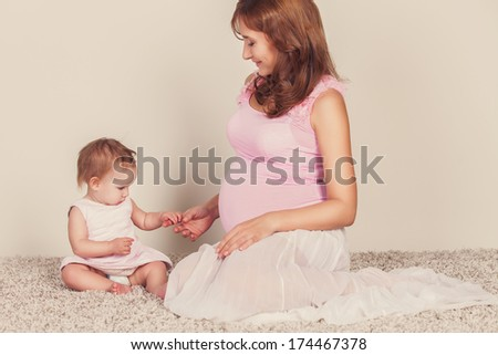 A pretty pregnant woman playing with her daughter - stock photo