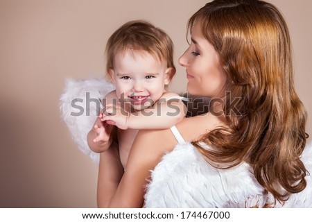 A pretty pregnant woman playing with her daughter with angel wings - stock photo