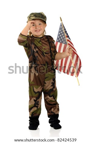 """A pretty preschool """"soldier"""" happily solutes while holding an American flag.  Isolated. - stock photo"""
