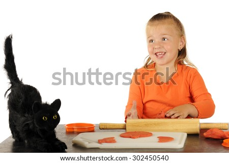 A pretty preschooler happily cutting Halloween decorations from modeling clay.  A scary black cat sits near her working space. - stock photo