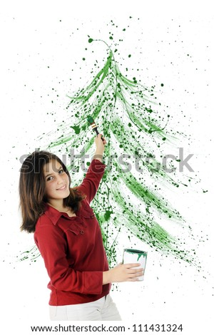 A pretty preteen splattering green paint to creat a large image of a Christmas tree.  On a white background. - stock photo