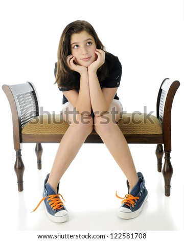 A pretty preteen wistfully sitting on a bench, her head propped by her hands, knees together and feet spread.  She's wearing shorts and over-sized, unlaced high-top sneakers.  On a white background. - stock photo