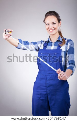 A pretty smiling woman holding a long tape measure