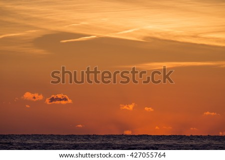 A pretty sunrise sky with some clouds over the ocean.