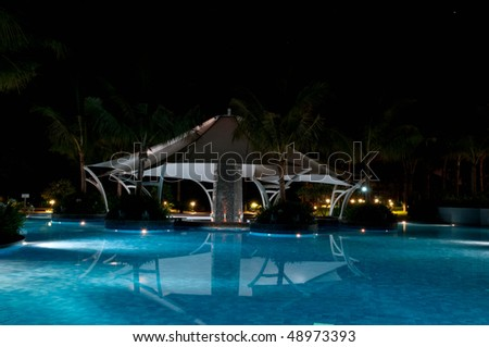A pretty swimming pool in night at a local resort - stock photo