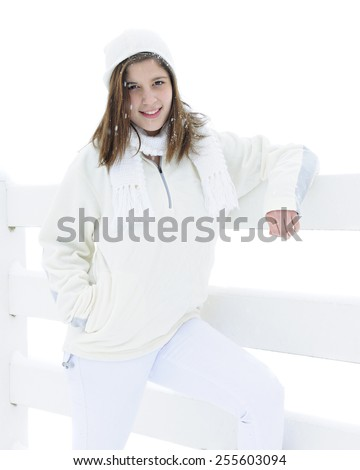 A pretty teen brunette wearing white in the snow by a snowy white fence.  On a white background. - stock photo