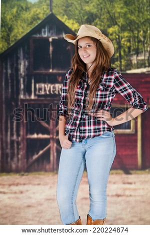 A pretty teen cowgirl standing in front of an old western livery.   - stock photo