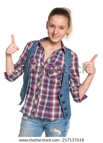 A pretty teen girl holds her thumbs up against the white background