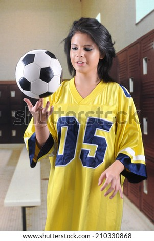 A pretty teen girl in an over-sized jersey in a locker room.  She's attempting to balance a soccer ball on one finger. - stock photo