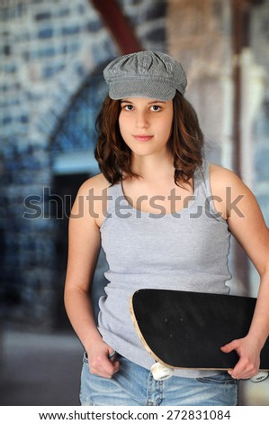 A pretty teen girl looking at the viewer as she's carrying her skateboard in an urban area. - stock photo