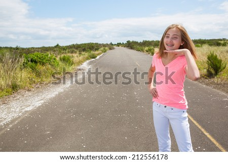 A pretty teen girl walking on an empty road in the country with bare feet - stock photo