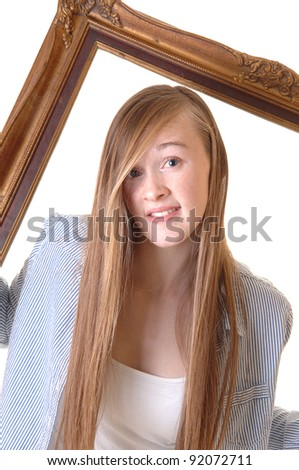 A pretty teenage girl in a blue striped shirt looking trough a picture frame, with her long blond hair and looking into they camera, for white background. - stock photo