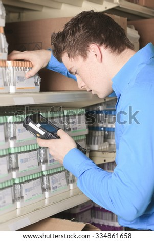A Pretty warehouse manager checking the inventory with a machine. - stock photo