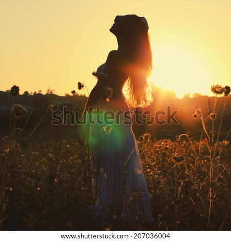 A pretty woman enjoying summer outside. Photo toned style Instagram filters - stock photo