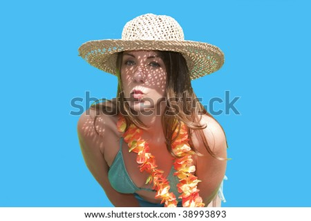 A pretty woman/girl in straw hat posing by blowing a kiss for the camera on a Hawaiian vacation. - stock photo