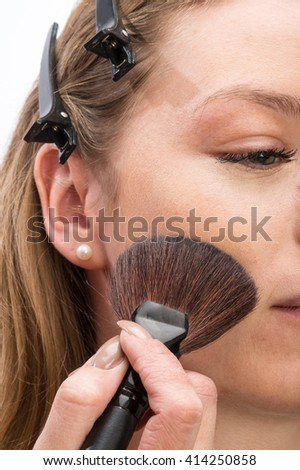 A pretty woman having make-up applied by a makeup artist. Close up.