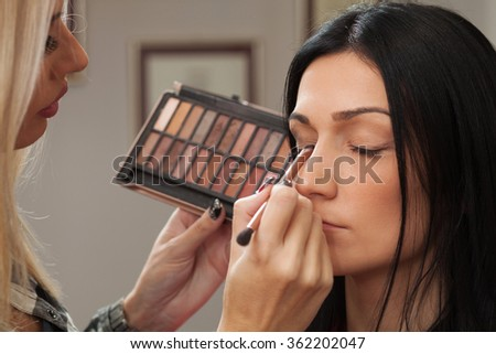 A pretty woman having makeup applied by a makeup artist