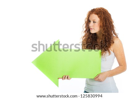 A pretty woman holding an arrow pointing left. - stock photo
