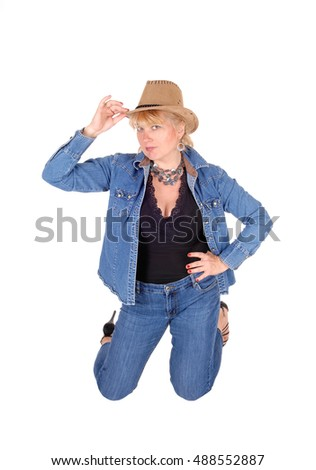 A pretty woman in jeans and jeans jacket kneeling on the floor, wearing