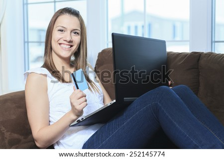 A Pretty woman makes purchases through the internet holding credit card - stock photo
