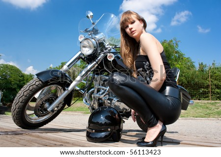 A pretty woman near by motorcycle  posing - stock photo