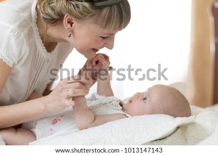 A pretty woman plays with a baby