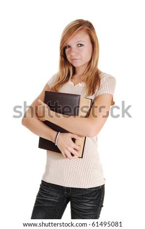 A pretty woman, standing in the studio and holding a big book on her chest, in gray jeans and beige sweater, for white background.