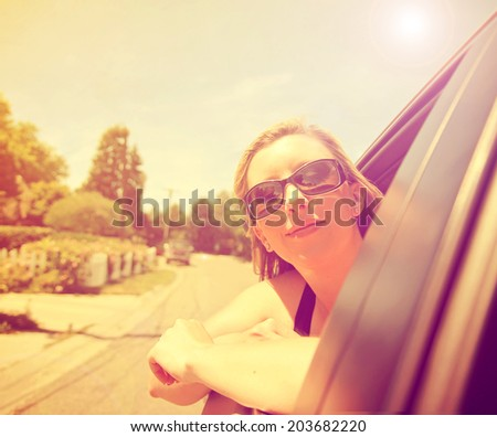 a pretty woman with her head out the window of a car driving down the street - stock photo