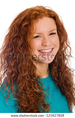 A pretty woman with naturally curly red hair and a happy, vibrant smile. - stock photo