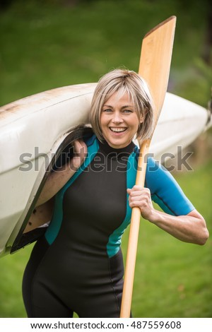 a pretty 40 year old woman with gray hair, she likes to play sports . she is going to join her husband . she does sport every weekend. she wears a wetsuit. she walks in carrying a kayak and a paddle
