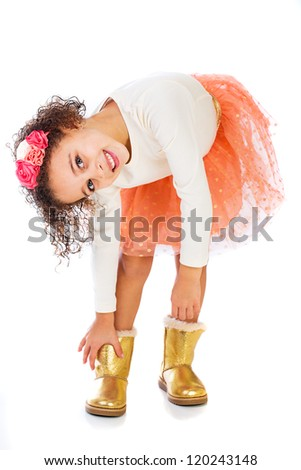 A pretty young African American girl putting on her gold boots. - stock photo